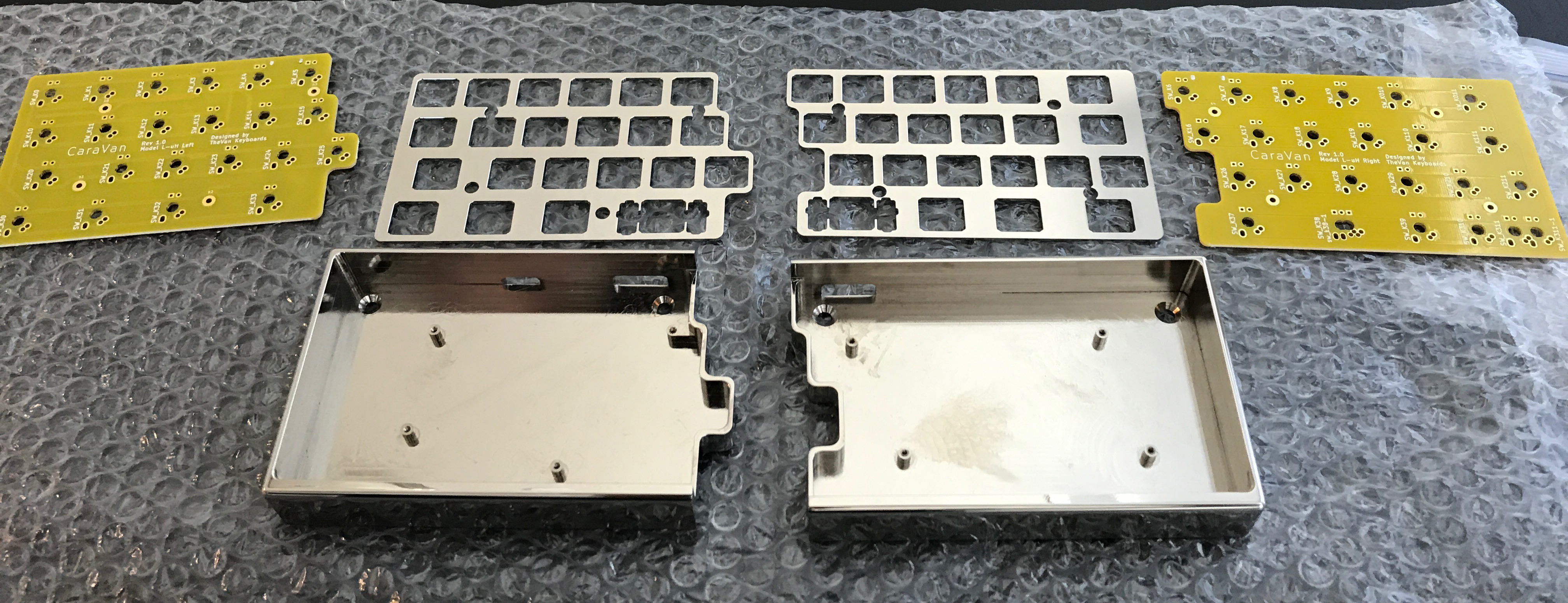 Unassembled CaraVan kit showing plates, cases, and top side of PCBs