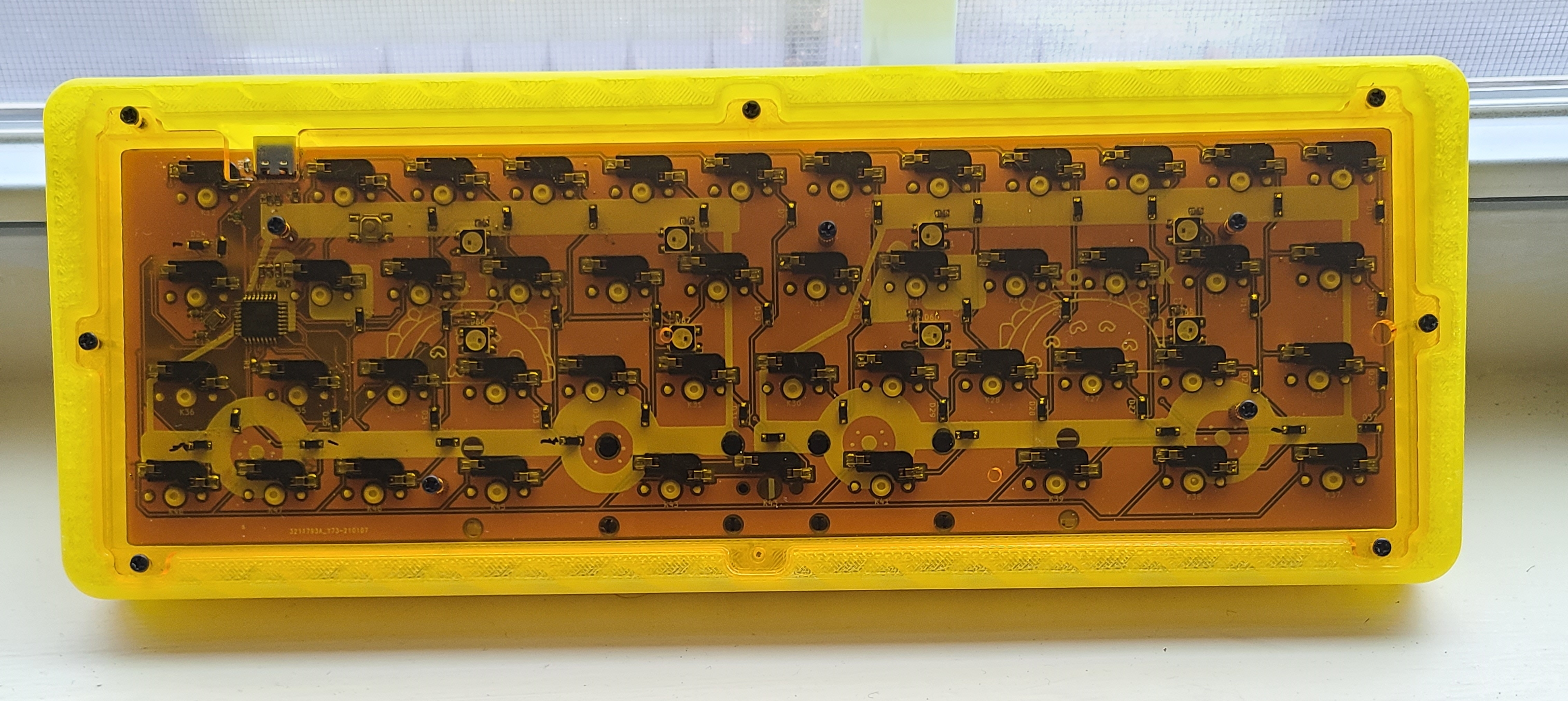 Underside of the PCB installed in a case. The hotswap sockets and misaligned USB port can be seen through the clear acrylic bottom.
